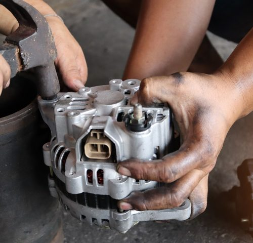 Change new car alternator with hand in the garage or auto repair service center, as background automotive concept. Dark tone.